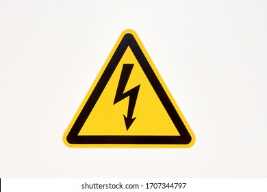 Danger sign of high voltage electricity. Yellow triangular label with a zipper in the center on the wall in the store