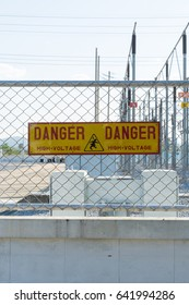 Danger sign high voltage on a mesh wire fence in front of substation