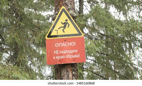 Danger sign of man falling from cliff. Stock footage. Sign hanging from tree warns tourists about cliff in coniferous forest. Sign with falling man with warning caption about cliff