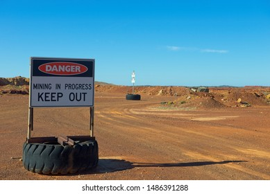 Danger Sign at Mining Site, with red sand and sunny blue background with copy space.