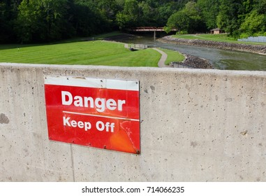 The danger sign on the cement wall overlooking the creek valley in the background.