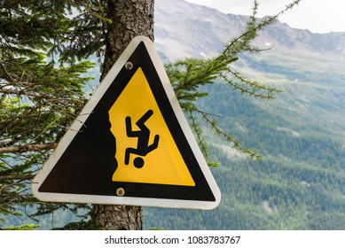 Danger sign on a mountain trail in the Alps. Attention to the precipice. Sign for the safety of hikers, placed on a larch in the high mountains