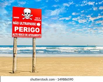 "Danger sign on a paradise beach in Brazil on summer. It is in portuguese, written ""Danger, no trespassing""."