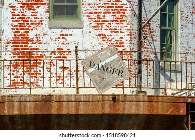Danger sign on Point No Point Lighthouse in Chesapeake Bay, USA on rusty aging metal banister and peeling red brick.