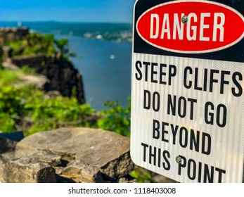 Danger sign for steep cliffs in foreground with cliffs and water in background.