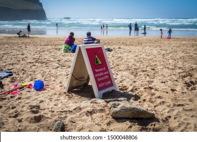 Danger sign warning beach users of potential unstable sand dunes and cliffs in Cornwall, UK
