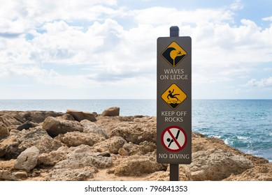 danger sign, waves on ledge, keep off rocks, no diving, seen on the beach in Oahu, Hawaii, US