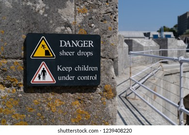 Danger sudden drop sign yellow warning triangle with symbol of man falling from a cliff edge and keep children under control sign on rampage