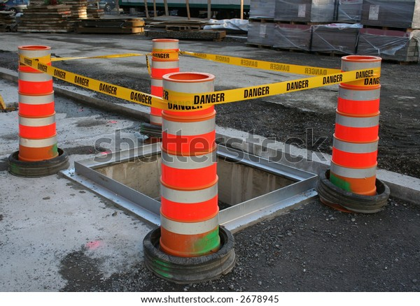 danger tape barrier around deep hole at construction site