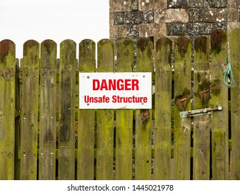 Danger Unsafe Structure sign on a wooden fence