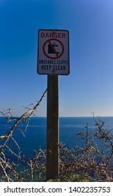 Danger Unstable Cliffs Keep Clear Sign with blue sky and sea in background