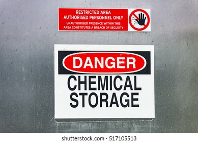 Danger warning sign for chemical storage in restricted area. English language danger chemical storage warning sign labels on large steel wall