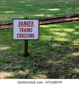 Danger warning sign next to a zoo rail line advising pedestrians to be careful
