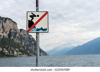 Danger warning sign on the shore of Lake Garda in Italy