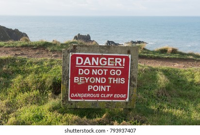 """Danger-Do Not Go Beyond This Point-Dangerous Cliff Edge"" Sign at Hartland Quay on the South West Coast Path with the Atlantic Ocean in the Background in Rural Devon, England, UK"