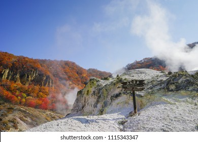 Danger/Keep out Sign at at Noboribetsu Jigokudani or Hell Valley in Hokkaido, Japan. Autumn season, red leaves, blue sky and sulfur gas steaming out from ground.