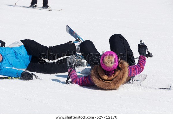Dangerous accident: the collision and fall of skiers. Women lying in the snow.