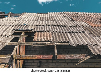 Dangerous asbestos roof. Asbestos dust in the environment. Health problems