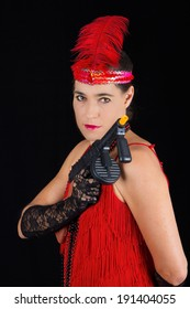 Dangerous beautiful brunette in 1920 style attire red dress feather and a gun