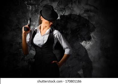 Dangerous and beautiful criminal girl with gun on grey wall