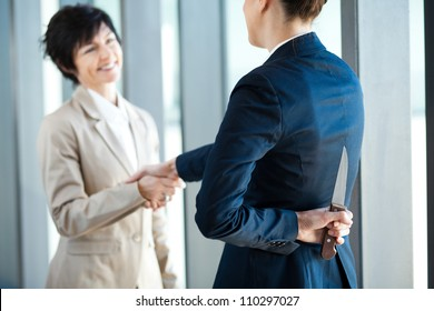 dangerous businesswoman holding knife behind her back while handshake