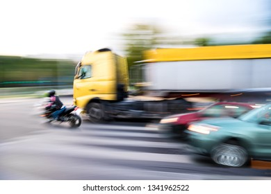 Dangerous city traffic situation with a motorcyclist and a truck in motion blur