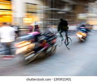 Dangerous city traffic situation with a motorcyclist and cyclist in motion blur. Defocused image
