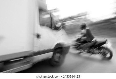 Dangerous city traffic situation with motorcyclist and car in the city in motion blur. Defocused image