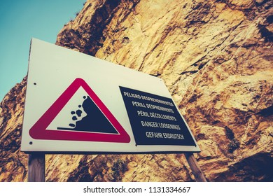 A Dangerous Cliff Face With A Warning Sign