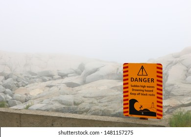 Dangerous Cliff Warning Sign in Peggy's Cove on a Foggy Day.