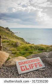 Dangerous cliffs sign in front of steep cliff by lands end in england, with the sea and sky in the background