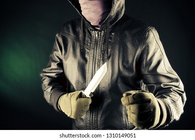 Dangerous criminal hold knife in hand.Large sharp weapon ready for robbery or to commit a homicide. Assassin man.