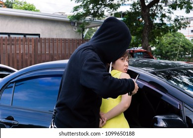 Dangerous criminal man with gun stealing car of scared young woman on outdoor parking.