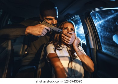 Dangerous criminal man with gun stealing car of scared young woman from the back seat in car.