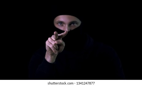 Dangerous criminal showing watching you gesture for intimidating victim, crime