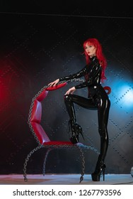 dangerous cruel fetish girl with red hair posing in black bdsm latex clothes at the chair from the chains in the style of sadomasochism