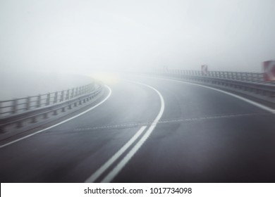 dangerous and curved road in serious foggy weather. intended motion blurred image