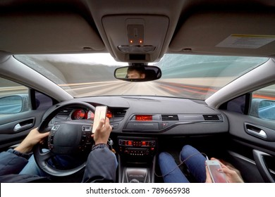 Dangerous driving while writing SMS text message. Man with momile phone in hand and young woman in a car speedy driving on highway.