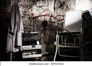 Dangerous electrical shocking device near medical gown hanging on the hanger and scary chair with blood stained wall for concept about torture or scary Halloween theme