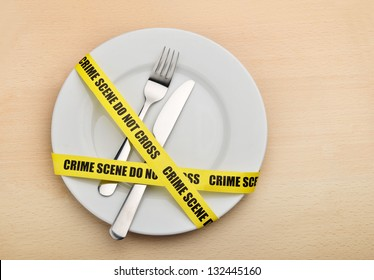 Dangerous food. Empty plate, fork and knife wrapped in crime scene tape.