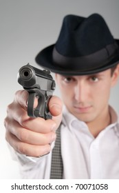 Dangerous gangster in hat holds a pistol and aims