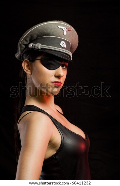 dangerous gorgeous girl with a german officer hat and a patch over a dark background