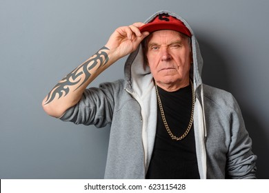 Dangerous grandad straightens his red cap. Old man's got gangsta style of clothes and a huge tattoo on his arm. An expensive gold chain completes his look.