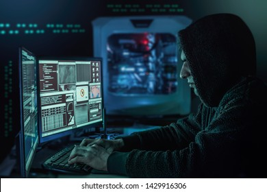 Dangerous hooded hacker in his hideout place which has a dark atmosphere, multiple displays