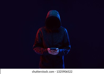 Dangerous hooded hacker. Internet, cyber crime, cyber attack, system breaking and malware concept. Dark face. Anonymous holding smartphone in hands.