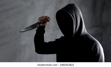 Dangerous hooded man standing in the dark and holding a knife Face can not be seen.