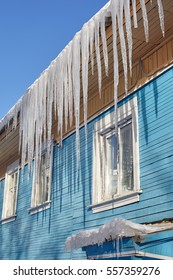 Dangerous icicles hanging from the roof of a wooden house