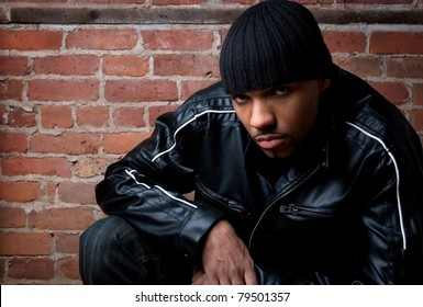 Dangerous looking guy dressed in black, sitting near a brick wall.