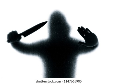 Dangerous man behind frosted glass with a knife in his hand. Halloween. Black and white image