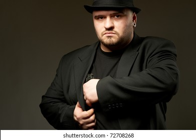 Dangerous man in black suite and hat with gun.